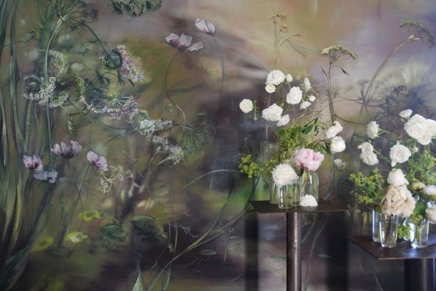 vingette of cut flowers from Claire Basler's garden against backdrop of her mural in home/studio outside Paris